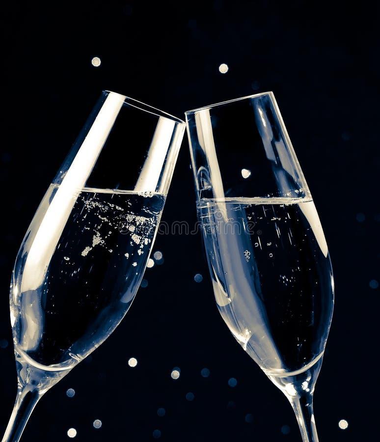 Duas flautas de champanhe no fundo claro escuro preto do bokeh fotografia de stock royalty free