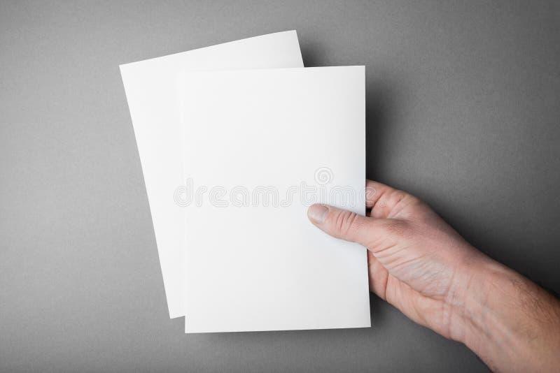 Duas folhas vazias do A5 para o projeto, um modelo na mão de um homem europeu foto de stock royalty free