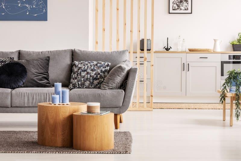 Duas formas de blocos de madeira como mesas de café com kinck tricacks em frente ao sofá cinza escandinavo com travesseiros foto de stock royalty free