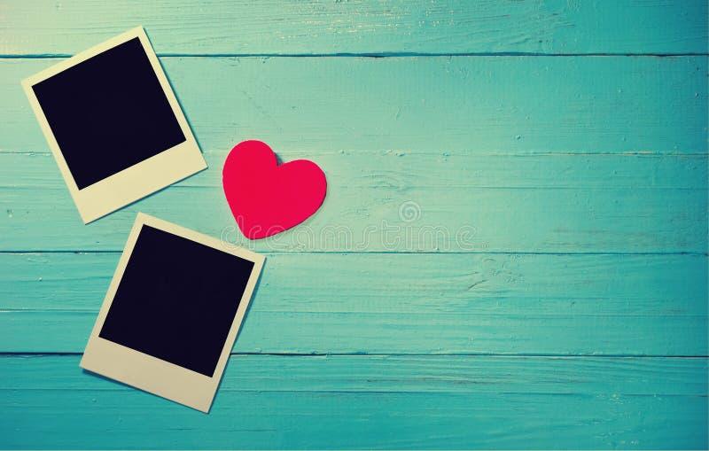 Duas fotos do polaroid com coração no fundo de madeira azul foto de stock royalty free