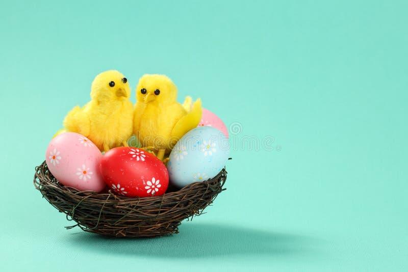 Duas galinhas decorativas bonitos que sentam no ovos pintados coloridos no fundo de turquesa da luz do ninho de um pássaro com es imagens de stock