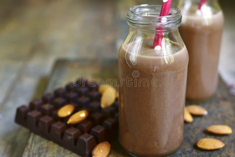 Duas garrafas da amêndoa do chocolate ordenham com palhas de papel imagem de stock