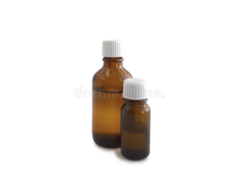 Duas garrafas da medicina com o óleo ou a droga isolado no fundo branco foto de stock