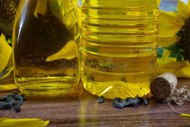 Duas garrafas do óleo vegetal estão na tabela, sementes, cortiça fotos de stock