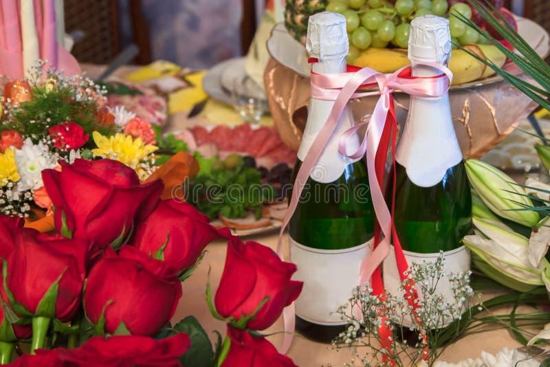 Duas garrafas do champanhe amarradas com uma fita no meio dos ramalhetes das flores, indicando um banquete de casamento ou o outr fotos de stock