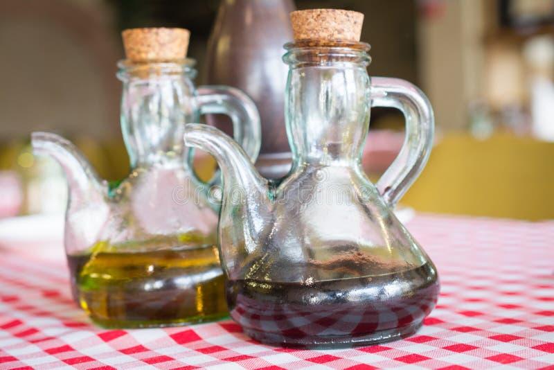 duas garrafas do vinagre balsâmico e do azeite em uma tabela fotografia de stock royalty free