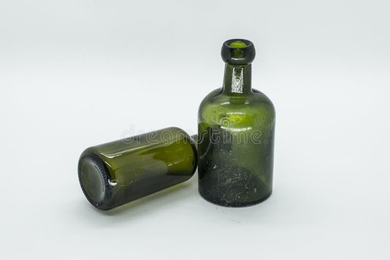 duas garrafas verdes velhas, uma posição e a outro que encontra-se isolado para baixo foto de stock
