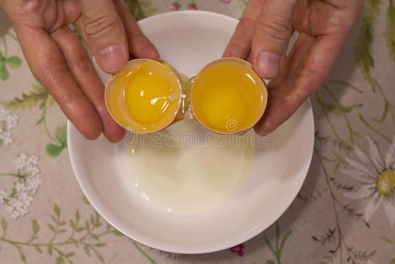 Duas gemas em um ovo 2 em 1 As mãos das mulheres abrem um ovo original com duas gemas O processo de abrir ovos para fazer o bolo, fotos de stock