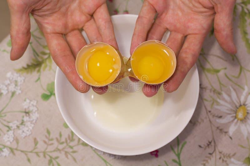 Duas gemas em um ovo 2 em 1 As mãos das mulheres abrem um ovo original com duas gemas O processo de abrir ovos para fazer o bolo, imagem de stock