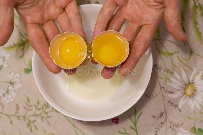 Duas gemas em um ovo 2 em 1 As mãos das mulheres abrem um ovo original com duas gemas O processo de abrir ovos para fazer o bolo, foto de stock
