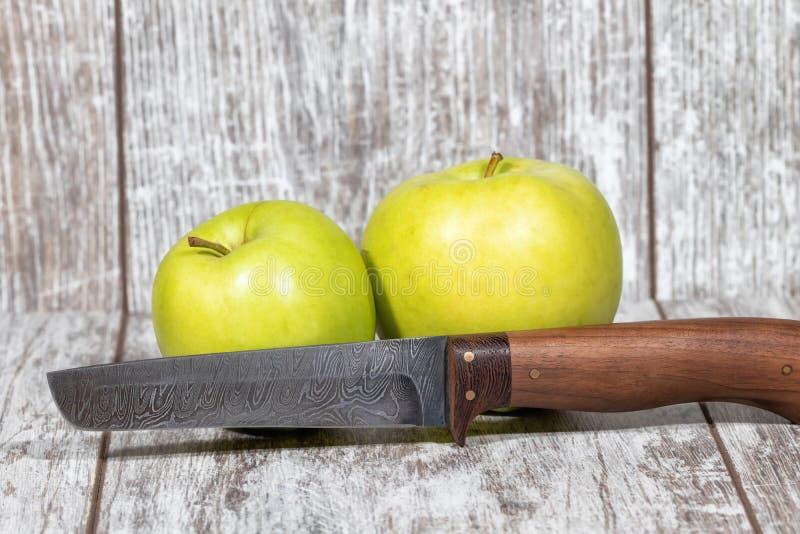 Duas grandes maçãs verdes e uma faca com uma lâmina do aço de Damasco fotografia de stock royalty free