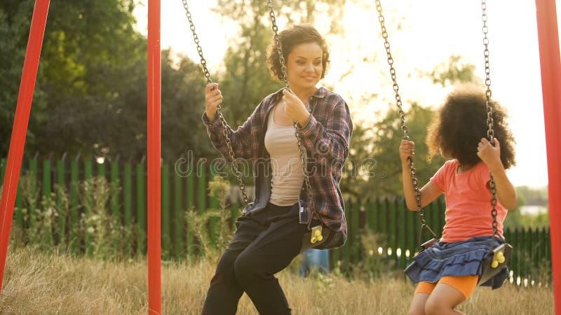 Duas irmãs alegres que balançam junto no campo de jogos exterior da criança, felicidade imagem de stock royalty free
