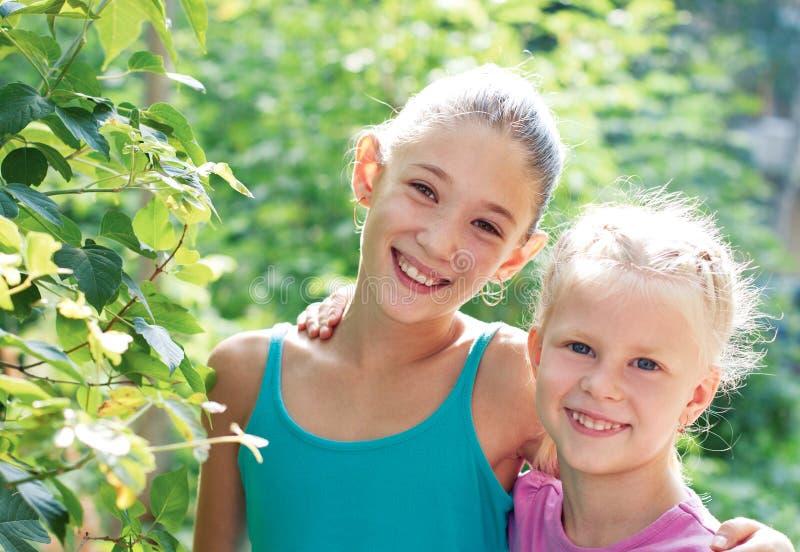 Duas irmãs alegres que jogam no parque no dia de verão morno imagem de stock