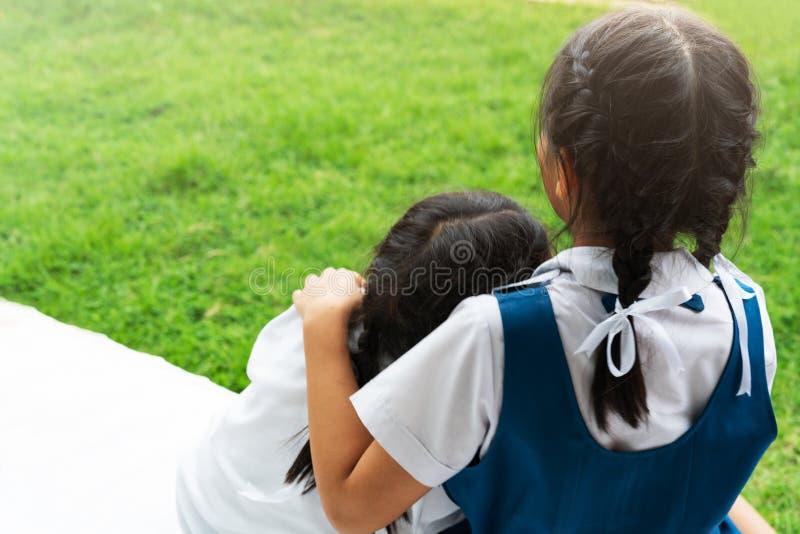 Duas irmãs asiáticas pequenas das meninas que abraçam o cargo feliz na farda da escola, de volta ao conceito da escola fotos de stock royalty free