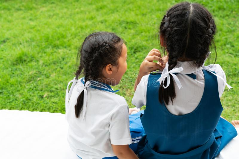 Duas irmãs asiáticas pequenas das meninas que abraçam o cargo feliz na farda da escola, de volta ao conceito da escola foto de stock