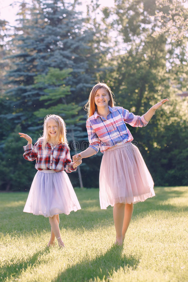 Duas irmãs caucasianos engraçadas de sorriso das meninas na camisa de manta e na saia cor-de-rosa do tule do tutu imagens de stock
