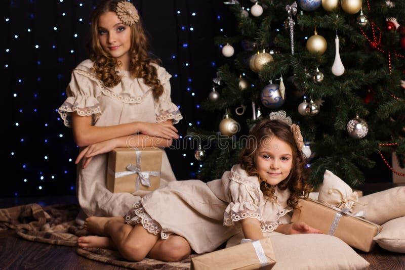 Duas irmãs com os presentes do ano novo aproximam o Natal imagens de stock
