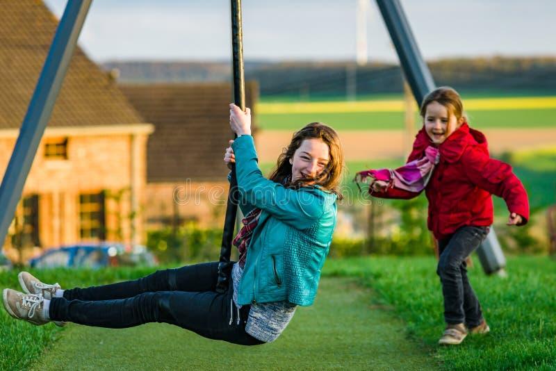 Duas irmãs: criança em idade pré-escolar e adolescente - jogando no campo de jogos foto de stock