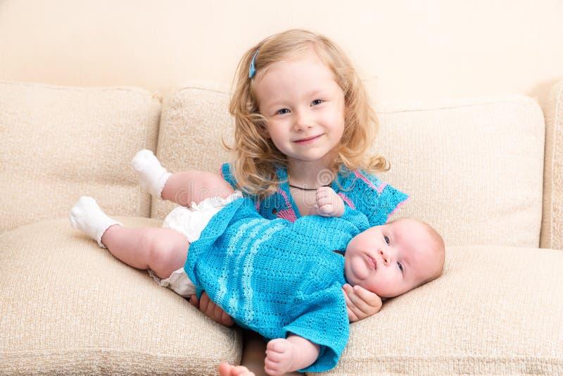 Duas irmãs Criança mais idosa da irmã que abraça sua irmã mais nova recém-nascida foto de stock
