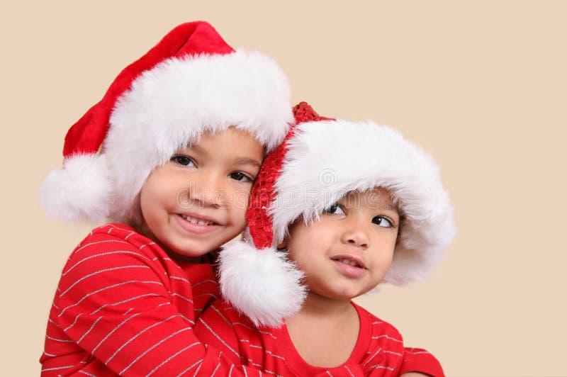 Duas irmãs da raça misturada em chapéus de Santa imagem de stock
