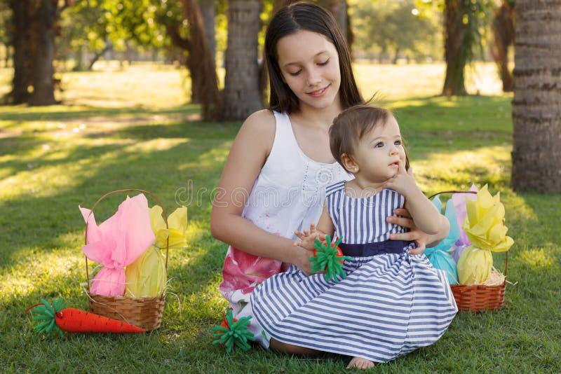 Duas irmãs das meninas: bebê e adolescente com os ovos de chocolate da Páscoa fotos de stock