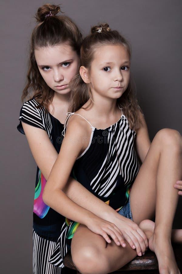 Duas irmãs das meninas de lado a lado em um fundo cinzento foto de stock