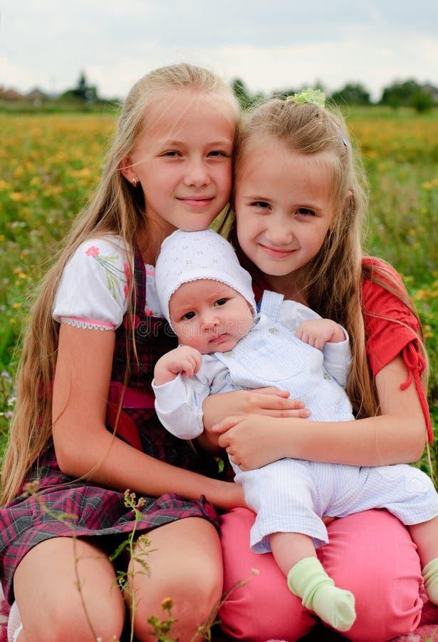 Duas irmãs e irmão imagem de stock