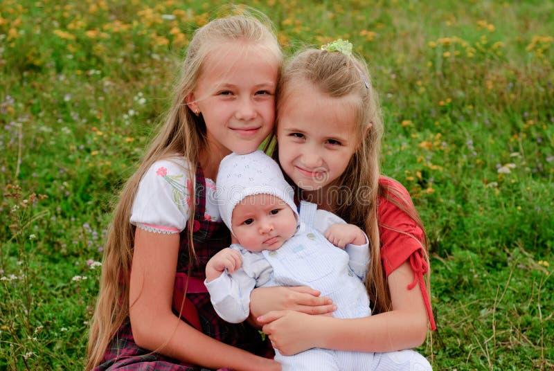 Duas irmãs e irmão fotografia de stock