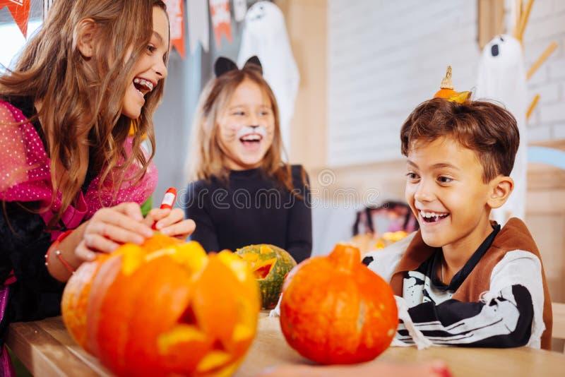Duas irmãs e um irmão que vestem os trajes de Dia das Bruxas que sentem felizes e alegres fotografia de stock