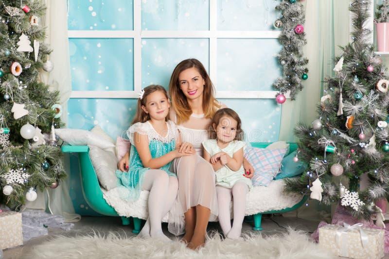 Duas irmãs e uma mãe nova em decorações de um Natal fotografia de stock