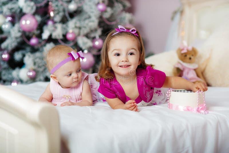 Duas irmãs em casa com árvore de Natal Retrato de decorações felizes das meninas das crianças foto de stock