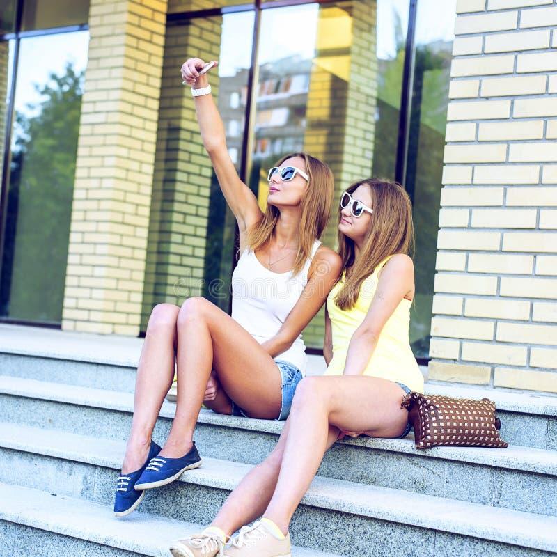 Duas irmãs em etapas do instituto estão fazendo o auto, trabalhos em rede sociais, vidros e short da sarja de Nimes foto de stock royalty free