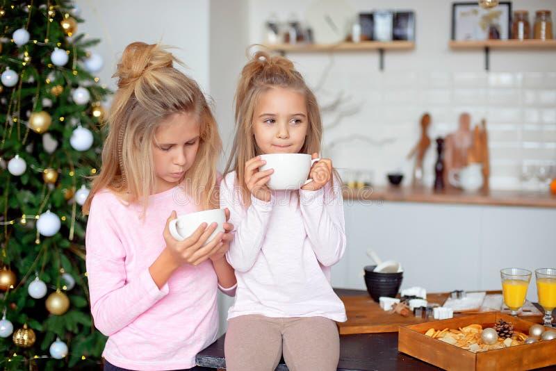 Duas irmãs em seus pijamas no chá bebendo da cozinha do copo branco grande no fundo da árvore de Natal fotografia de stock royalty free