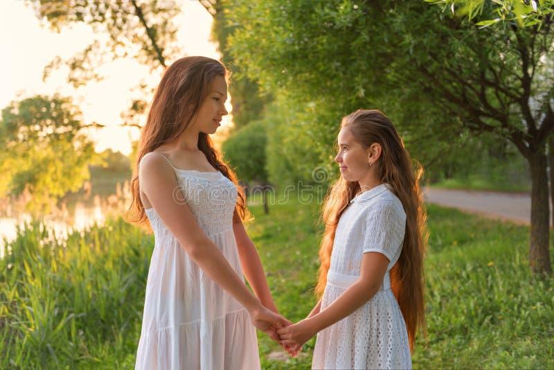 Duas irmãs em um branco simples vestem guardar as mãos que olham o olho para eye com o fundo do céu do alvorecer fotos de stock