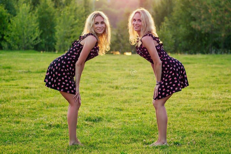 Duas irmãs engraçadas gêmeas lindas loiras e loucas e felizes mulheres sorriem de vestido estiloso se divertem no verão imagem de stock