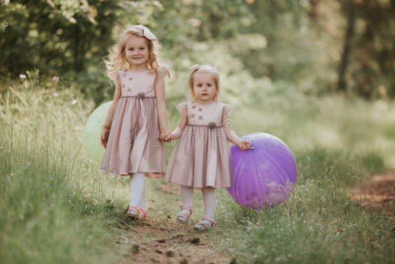 Duas irmãs estão jogando balões Miúdos que jogam junto Irmã feliz com balões que anda no campo da mola fotografia de stock royalty free
