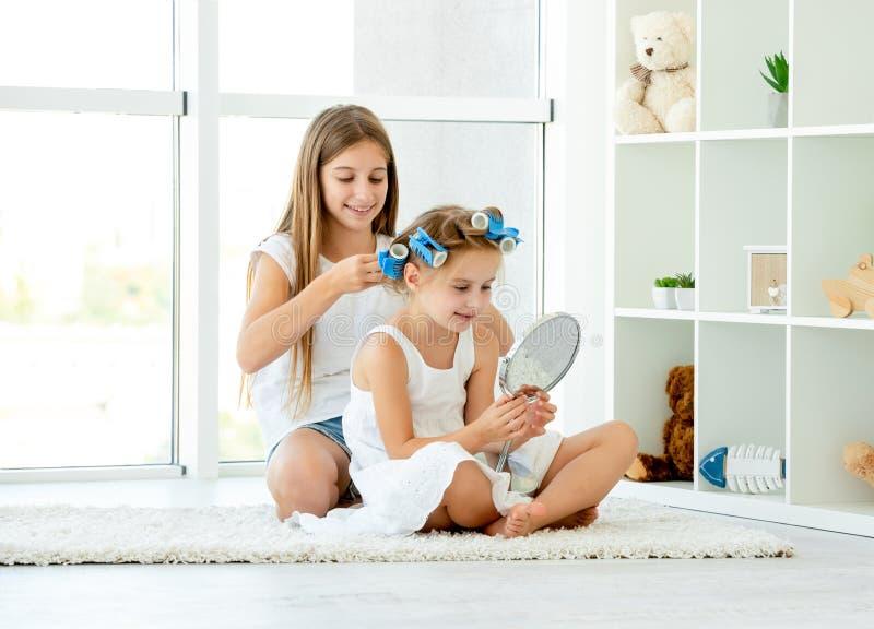 Duas irmãs fazendo beleza com curlers fotos de stock royalty free