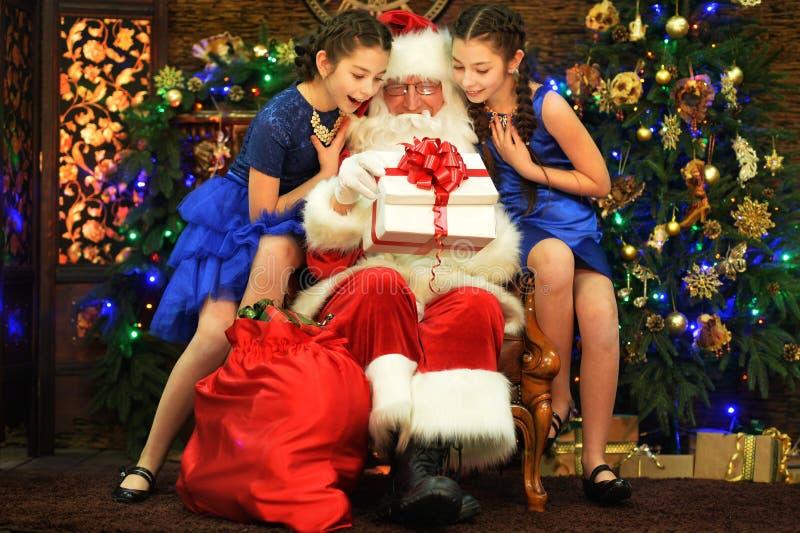 Duas irmãs gêmeas bonitas que sentam-se perto de Santa Claus imagem de stock royalty free