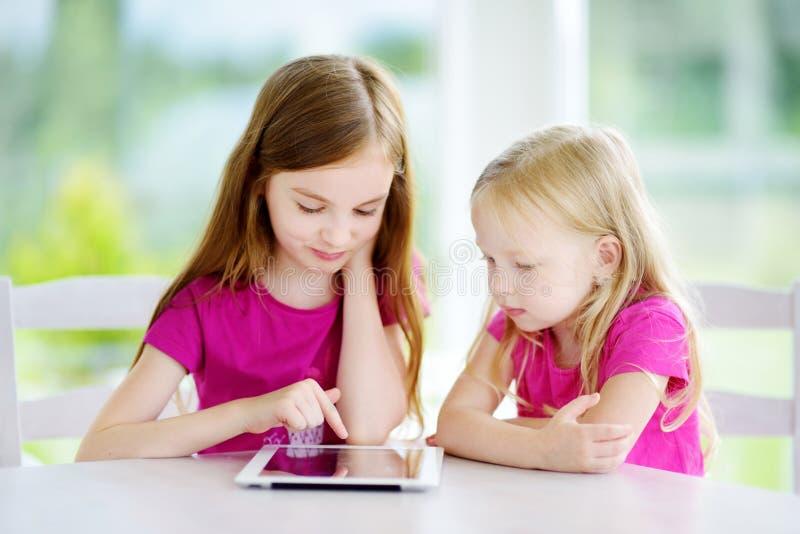Duas irmãs mais nova adoráveis que jogam com uma tabuleta digital fotos de stock