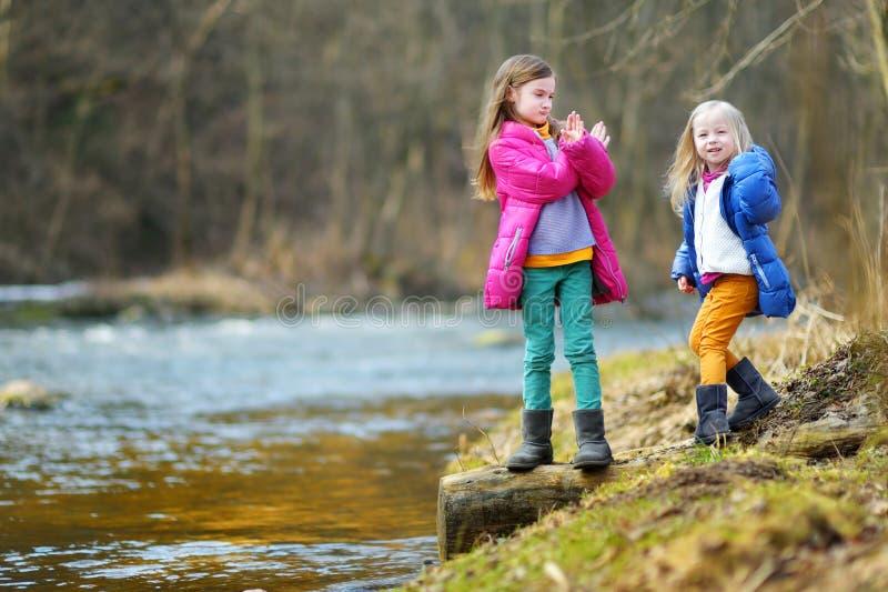 Duas irmãs mais nova bonitos que têm o divertimento por um rio fotos de stock