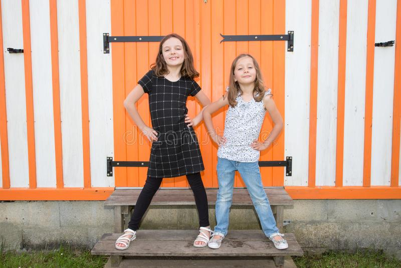 Duas irmãs mais nova bonitos que têm a parte dianteira do divertimento da cabana de madeira alaranjada junto no lazer exterior do foto de stock