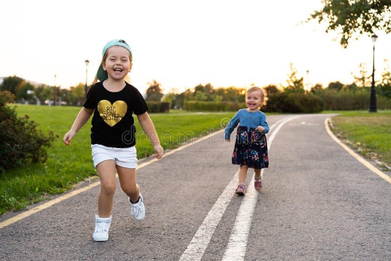 Duas irmãs mais nova correm na estrada no parque em um dia de verão ensolarado Meninas bonitos foto de stock royalty free