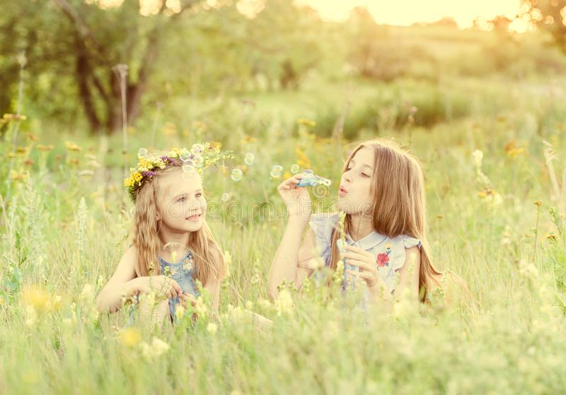 Duas irmãs mais nova que fundem bolhas de sabão fotos de stock