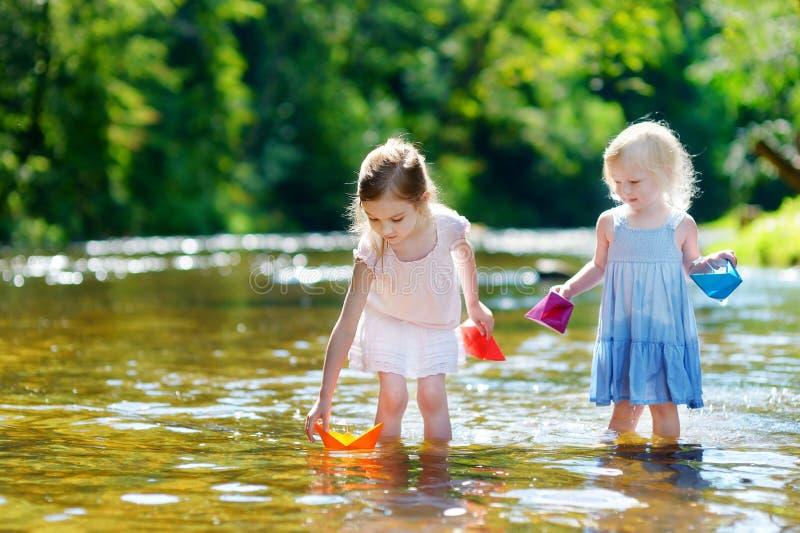 Duas irmãs mais nova que jogam com barcos de papel fotos de stock royalty free