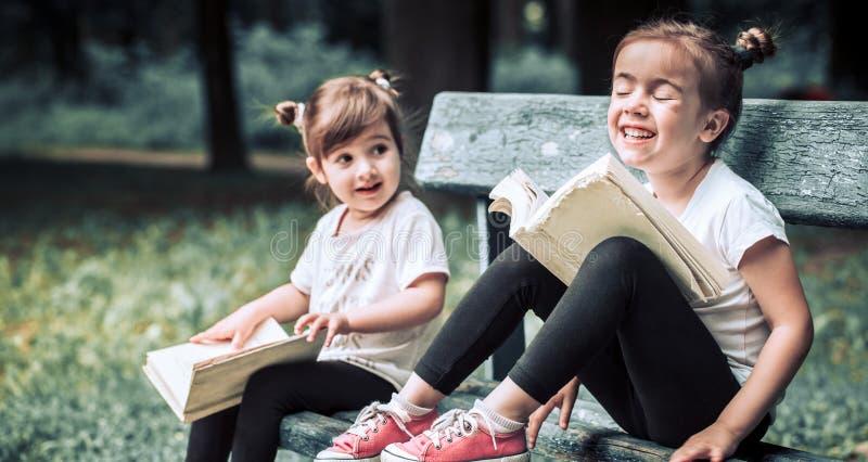 Duas irmãs mais nova que leem um livro foto de stock royalty free
