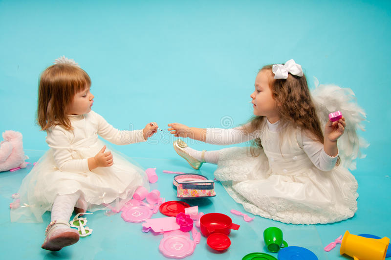 Duas irmãs pequenas bonitos que jogam com brinquedos foto de stock