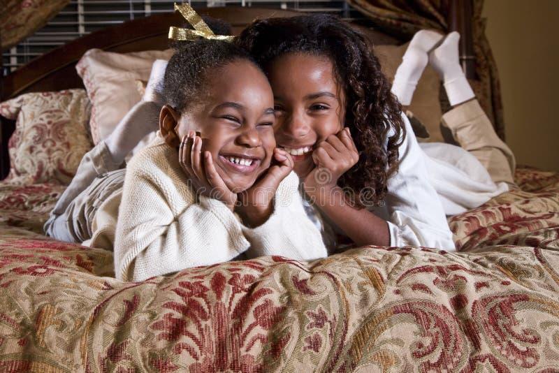 Duas irmãs pequenas com sorrisos felizes imagem de stock