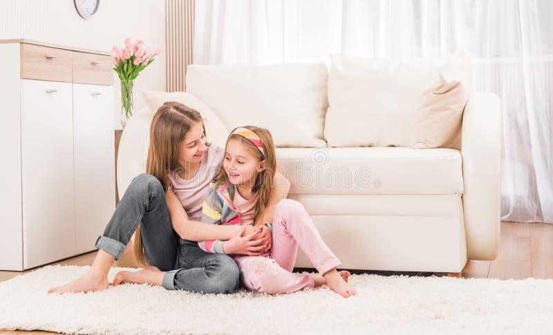 Duas irmãs que abraçam no assoalho fotografia de stock royalty free