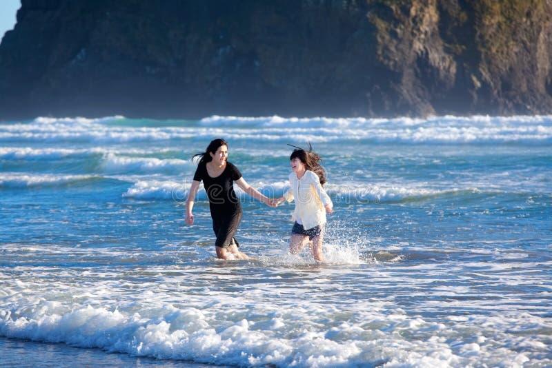 Duas irmãs que correm em ondas de oceano fotografia de stock royalty free