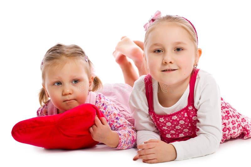 Duas irmãs que encontram-se no assoalho branco fotos de stock